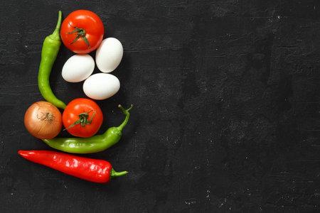 delicious to make tomato pepper egg and onion menemen standing on black background. Turkish omelette. Foto de archivo