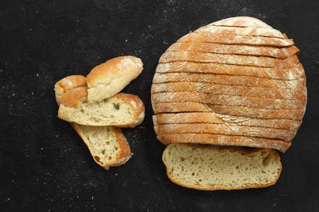 Sliced homemade sourdough rye bread with rye flour on black textured background. Top view or flat-lay. Low key