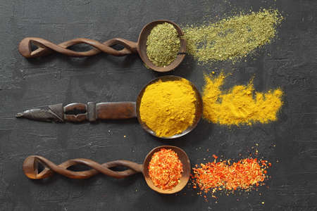 Different kind of spices on a black stone. Oriental spices in spoons, red peppers, curry powder, mint powder. Flat lay, top view. Foto de archivo