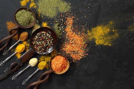 Different kind of spices on a black stone. Oriental spices in spoons, red peppers, curry powder, cinnamon powder, mint powder, colorful peppers. Flat lay, top view. Foto de archivo