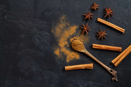 Aromatic cinnamon sticks, cinnamon powder and anise on black table, flat lay. Space for text
