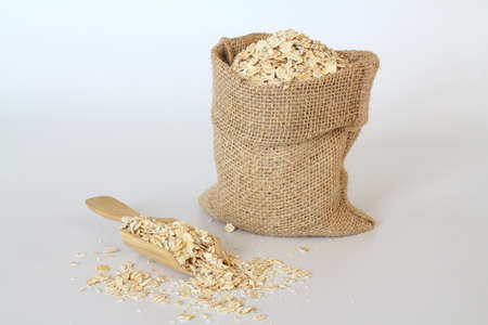 Oat flake in a sack and spoon on the white background. Heap of oats for package of oatmeal or granola