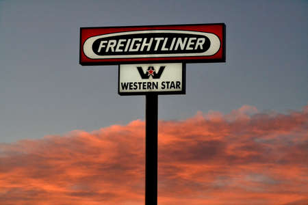 Freightliner truck sign with early moring clouds as background. Freightliner trucks is an American truck manufacturer.