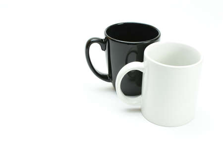white coffee mug in front of black coffee mug, high key
