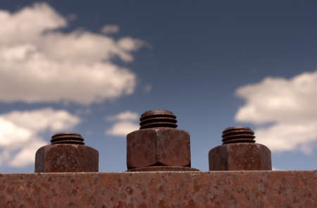 three rusty nuts and bolts on bridge with blue sky