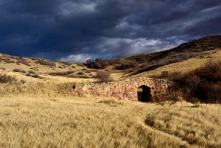 old rock footbridge in field of fall grasses Imagens