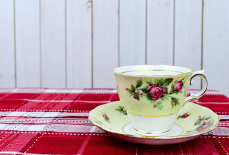 English tea cup and saucer on red tablecloth Imagens
