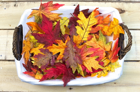 colorful fall leaves in a wicker basket Imagens