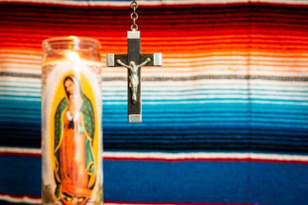 wood and silver crucifix with Virgin Mary prayer candle to the left, with Mexican blanket as backdrop. Cathoilc, Easter, religion concepts.