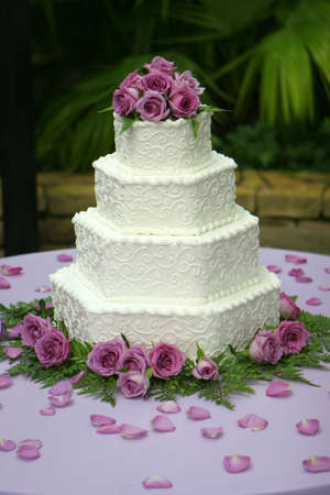 Beautiful multi-tiered wedding cake with white frosting.  The cake is decorated with purple roses.