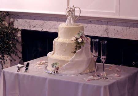 美しい多段ウェディング ケーキと黄色のアイシング。結婚式のカップルの上に花と、シャビエルで飾られています。お祝いシャンパン グラス幸せな