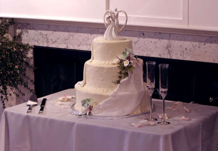 Beautiful multi-tiered wedding cake with yellow icing. Adorned with flowers and a ceremic wedding couple on top. Celebration Champagne glasses await the happy couple. photo