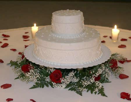 2 階層の結婚式のケーキのクローズ アップのバラの花びらに囲まれています。キャンドルの効果のためのケーキを照らします。