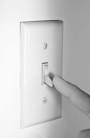 conserve: Finger shutting off Light Switch to Conserve Power.