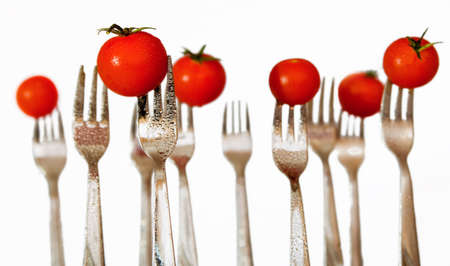 Water sprayed forks with cherry tomatoes with white background.  Stock Photo