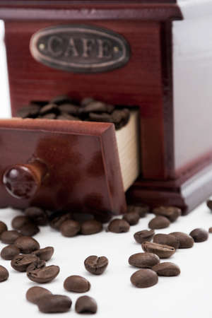 Dispersed coffee beans with coffee grinder in the background Stock Photo