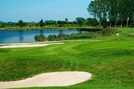 Campo de golf con verdes, lago, arena y taladro 17 bandera