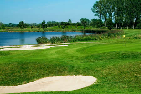 Golf field with green, lake, sand and hole 17 flag photo