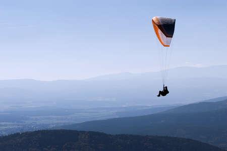A parachutist flight through the landscape close to horizon Stock Photo