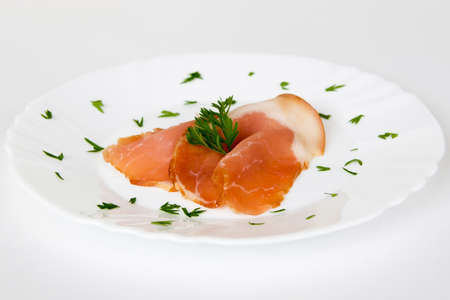 two ham slices on a white plate with green decoration