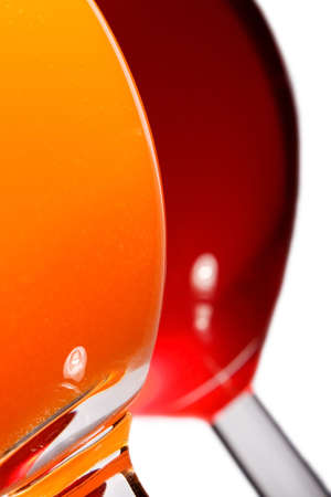 glass curves with juice (orange and cherry) and reflection of light