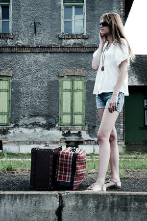 Young lady phone on the platform with old fashioned suitcases Stock Photo