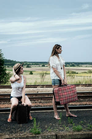 Young ladies with old suitcases on a platform photo