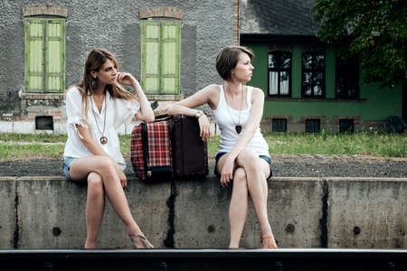 Young ladies with old suitcases on a platform Stock Photo