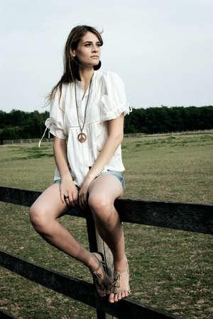 Beautiful young lady sit on paddock