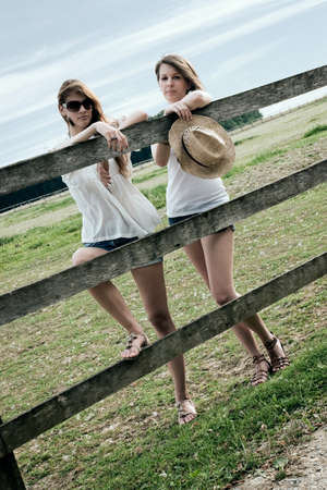 Two beautiful young ladies are posing at paddock