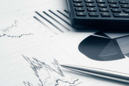 Business background with finance graphs, pen, and calculator