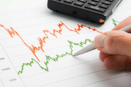 Businessman point to financial graph with pen.