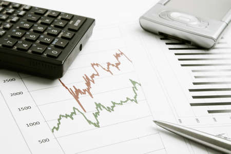 Business background with finance graphs, pen, calculator and PDA Stock Photo