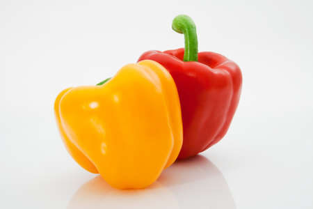 Red and yellow sweet peppers macro on a white background