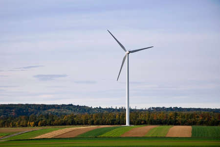 Wind turbine with autumn forest and fields