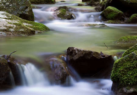 two little cascades in the forest with moss and rocks