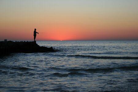Gentleman fishing at sunset from a rocky pier in beautiful Sarasota, Florida.