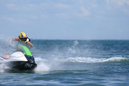 Jetski rider manuvers around a bouy in competition.