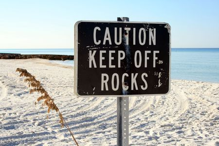 Beachside warning sign to keep off rocks.  Shot in beautiful south Florida.