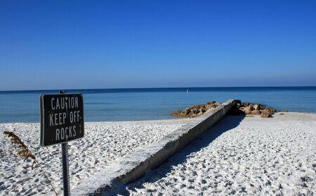 Beachside warning sign to keep off rocks.  Shot in beautiful south Florida.
