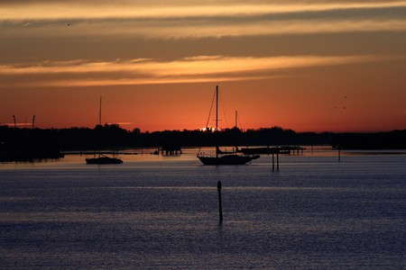 Sunrise at a marina in south Florida.  Beautiful colors accent the background while silhouettes of sailboats complete this scene.