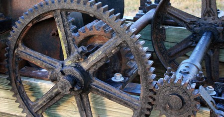 Antique gears and cogs on an old machine.  Possibly an old water pumping device.