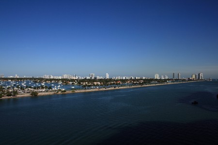 Panorama Shot of South Beach Florida.  Sailboats, palm trees, and office building all populate the scene.