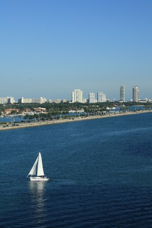populate: Shot of South Beach, Miami, Florida.  Sailboats, palm trees, and office building all populate the scene.