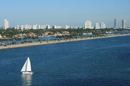populate: Panorama Shot of South Beach Florida.  Sailboats, palm trees, and office building all populate the scene.
