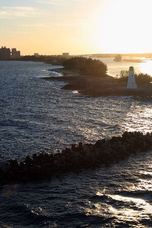 Lighthouse on Paradise Island in Nassau, Bahamas.  Shown in early morning at sunrise.  The Atlantis Resort can be seen in the distance.