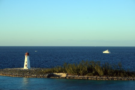 Lighthouse on a small island in the Bahamas.  A yacht is shown passing in the background.