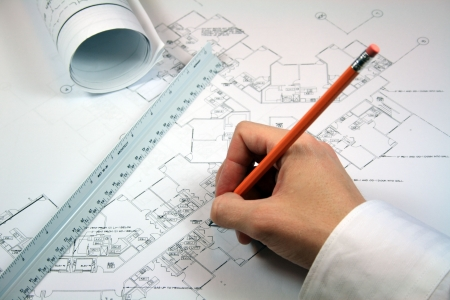Architect working with blueprints.  Workspace includes rolled blueprints and architect ruler.