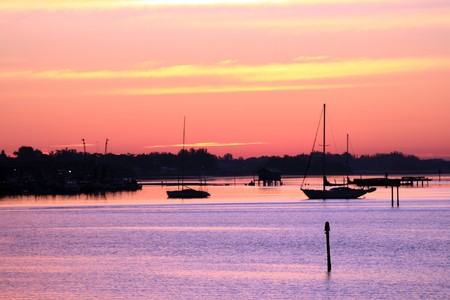 Early morning sailing in Sarasota, Florida.  Boats anchored on the bay before sunrise. Stock Photo