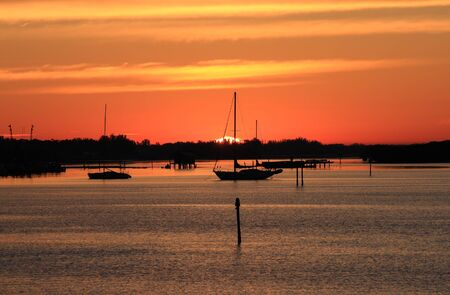 Early morning sailing in Sarasota, Florida.  Boats anchored on the bay at sunrise. Stock Photo